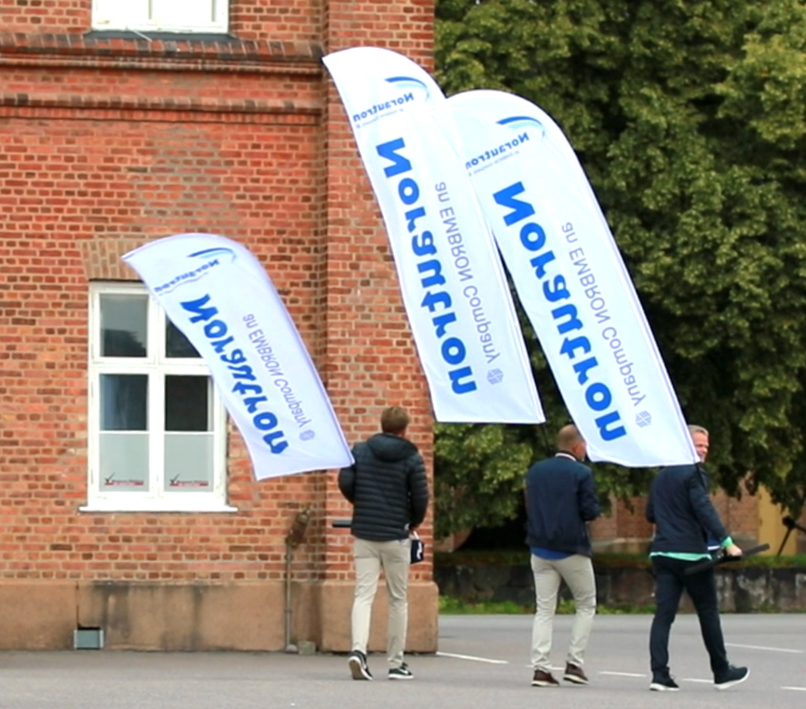 Norautron beach flags being carried by group of male employees.